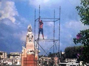 A TRE METRI D'ALTEZZA SENZA PROTEZIONE PER MONTARE IL PALCO PER IL CONCERTO DI DOMENICA